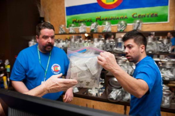 DENVER, CO - JANUARY 1: Sam Walsh, left, a budtender, and facility manager David Martinez set up marijuana products as the 3-D Denver Discrete Dispensary prepares to open for retail sales on January 1, 2014 in Denver, Colorado. Legalization of recreationa