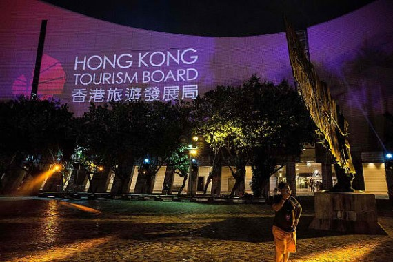 HONG KONG - JULY 17: Spectators look at the 3D light show on the wall of Hong Kong Cultural Centre and Clock Tower on July 17, 2015 in Hong Kong.